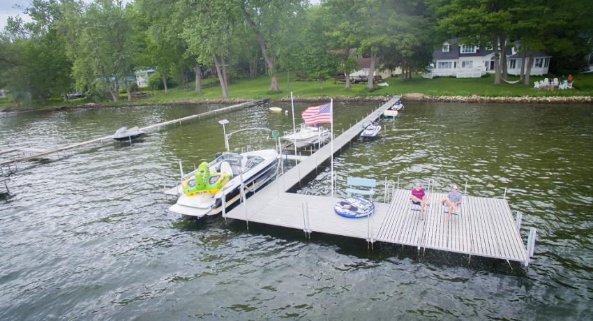Aerial aluminum dock on lake with people, boat and the American flag